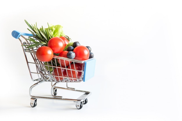 Shopping trolley full of fresh vegetables groceries isolated Premium Photo