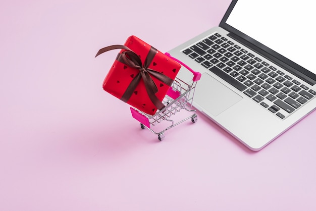 Shopping trolley and gift near modern laptop Free Photo
