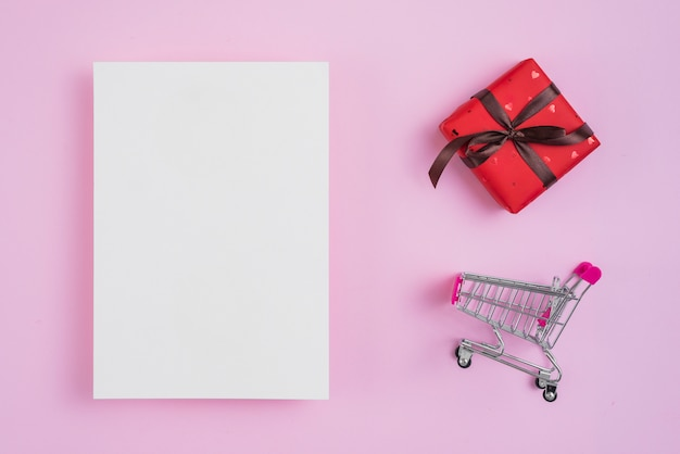 Shopping trolley and gift near paper sheet Free Photo