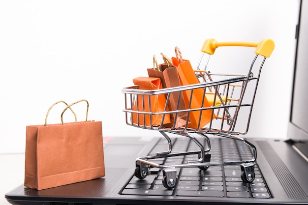 검은 노트북, 흰색 배경, 트롤리에 작은 종이 가방, 복사 공간, 온라인 쇼핑 개념에 쇼핑 트롤리 프리미엄 사진