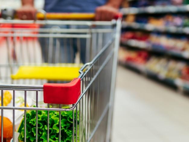 Shopping trolley in supermarket aisle Premium Photo