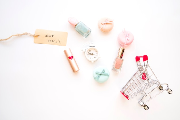 Shopping trolley with little alarm clock, macaroons, sale tag, lipstick and nail polish Free Photo