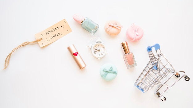 Shopping trolley with little snooze, macaroons, sale tag, lipstick and nail polish Free Photo