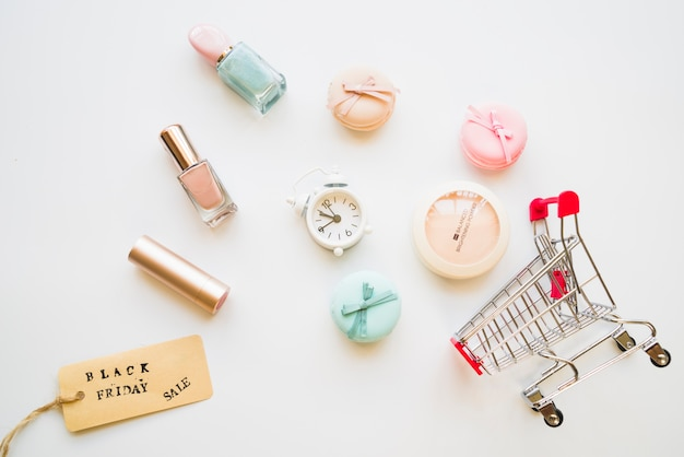 Shopping trolley with little snooze, macaroons, sale tag and nail polish Free Photo