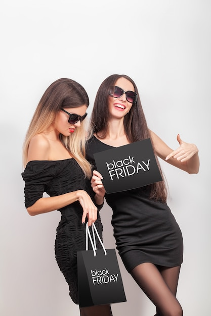 Shopping. two women holding black bags in black friday sales Premium Photo