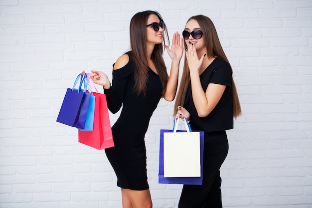 Shopping. two women holding black bags on light background in black friday holiday Premium Photo