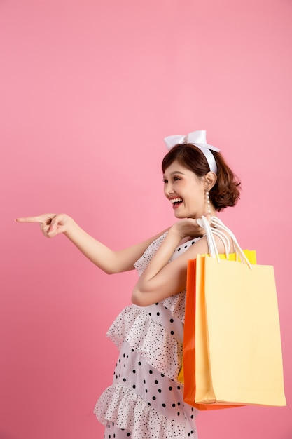 Shopping woman holding shopping bags on pink Free Photo