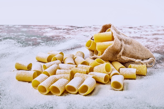 Short cut pasta in a sack on wooden table. Free Photo