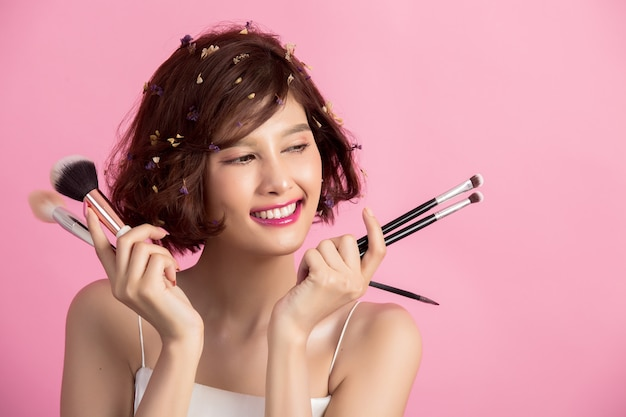 Short hair asian young beautiful woman applying cosmetic powder brush Free Photo