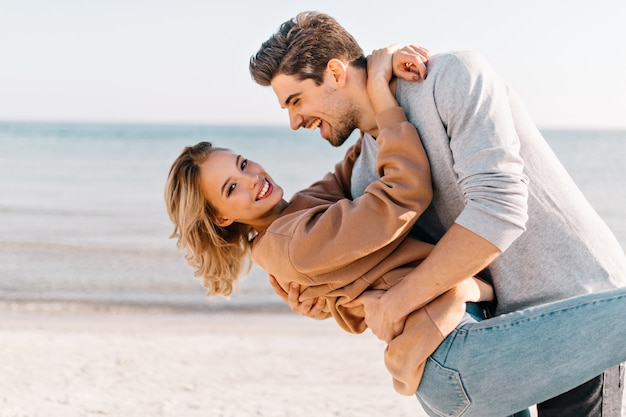 Short-haired blonde lady embracing husband in the beach. outdoor portrait of good-humoured man dancing with girlfriend near ocean. Free Photo