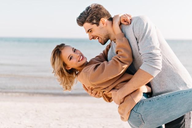 Блондинка с короткой стрижкой обнимает мужа на пляже. открытый портрет добродушного человека, танцующего с подругой на берегу океана. Бесплатные Фотографии