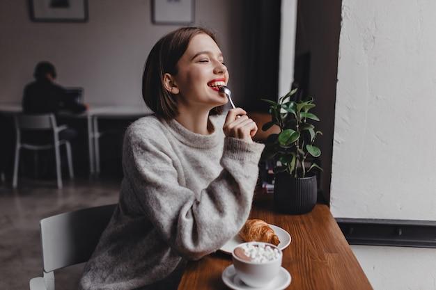 灰色のセーターを着た短髪の女性が小さじ1杯を噛みます。カフェに座ってクロワッサンとカプチーノを楽しんでいる赤い唇を持つ少女の肖像画。 無料写真