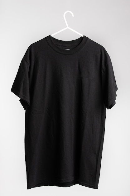 Short sleeve shirt on cloth hanger with white wall in the background Free Photo
