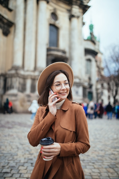 彼女の電話で写真とテキストメッセージで話している軽い帽子のショートヘアの女性 無料写真