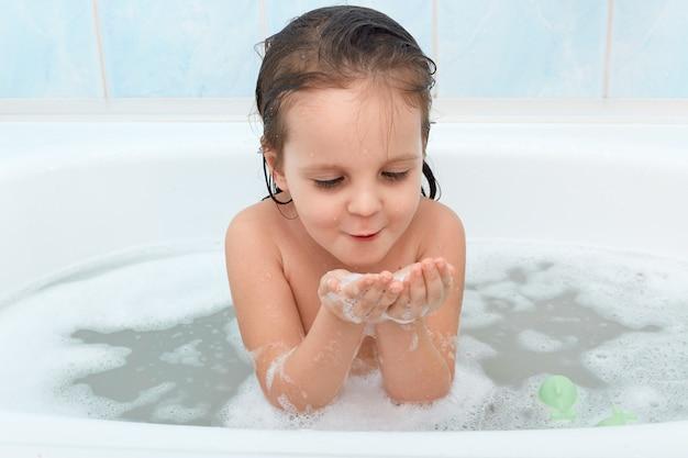 Colpo di adorabile bambina con i capelli bagnati, giocando con schiuma di sapone nella vasca da bagno Foto Gratuite
