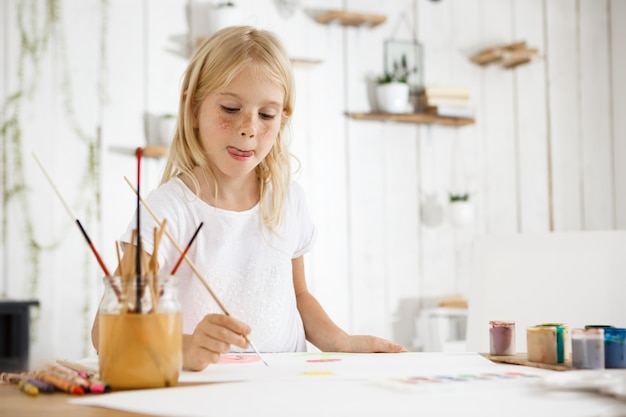 Shot of adorable blonde girl with freckles biting her tongue because of inspiration while painting. girl with blond hair sitting at the room filled with morning light and wearing white clothes. Free Photo
