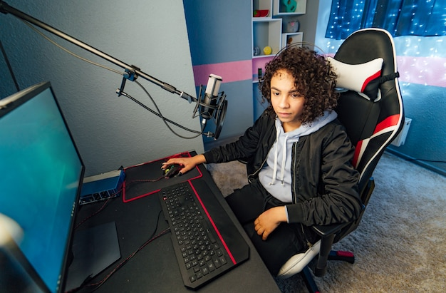 Shot of the beautiful pro gamer girl playing in first-person shooter online video game on her personal computer. neon room. esport cyber games internet Premium Photo
