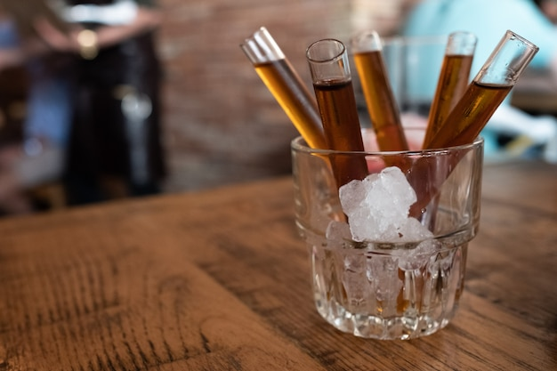 Shot of candy vodka in glass tube inside glass with ice Premium Photo