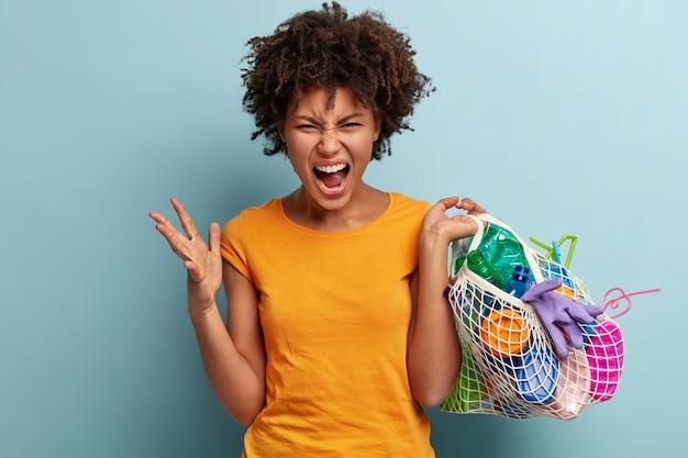 Inquadratura di una giovane donna disperata e arrabbiata che fa gesti con rabbia, trasporta un oggetto di plastica in una borsa a rete, infastidita dalla contaminazione, indossa una maglietta arancione, si erge contro il muro blu. concetto di consapevolezza di plastica Foto Gratuite