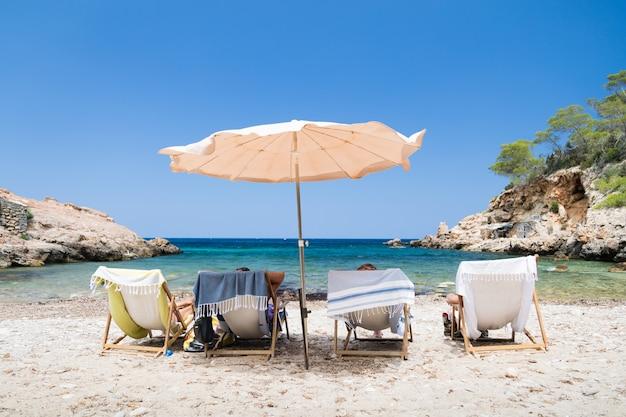 Colpo di quattro persone in lettini sulla spiaggia Foto Gratuite