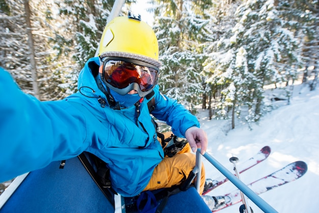 Shot of a fully equipped skier wearing skies, yellow helmet and skiing mask taking a selfie while riding the ski lift in the mountains Premium Photo