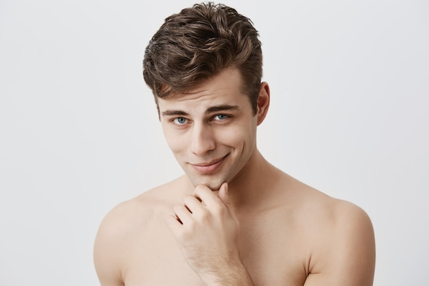 Shot of handsome attractive young caucasian male expressing positive emotions as has good mood after walk with girlfriend. pleasant looking guy smiles  holding hand under his chin. Free Photo
