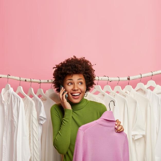 Colpo di felice donna afroamericana sceglie nuovi vestiti in showroom, preleva dolcevita viola sui ganci, sta sopra una serie di vestiti bianchi sui ganci Foto Gratuite