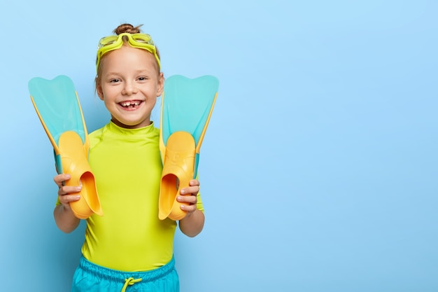 Shot of happy ginger small girl shows new rubber flippers, wears swim goggles, dressed in summer clothes, enjoys learning swimming, has active rest, isolated on blue wall with blank space Free Photo