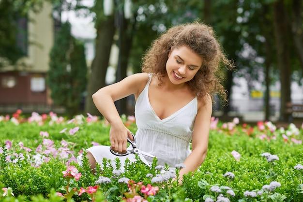Il colpo di una giovane donna felice che fa il giardinaggio sorridendo con gioia la ricreazione di godimento del copyspace si rilassa il concetto vivente della casa della campagna di feste di fine settimana. Foto Gratuite