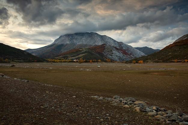 Colpo di terreno con sabbia sul fronte con montagne rocciose con leggera neve Foto Gratuite