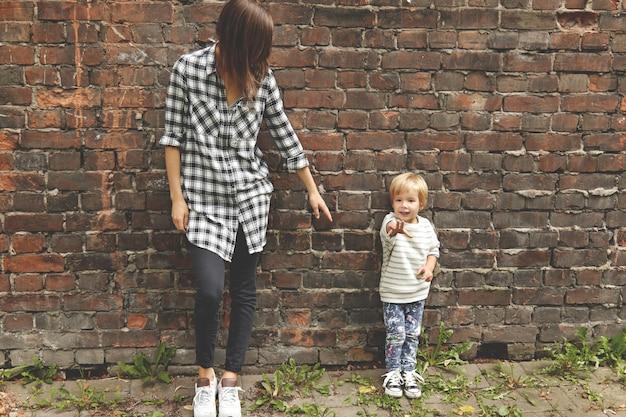 Colpo di ragazzino con sua sorella premurosa vicino al muro di mattoni. magrissima ragazza caucasica vestita con camicia a quadri, pantaloni neri. allunga il braccio al fratello minore, ma lui gli tira la mano in avanti. Foto Gratuite