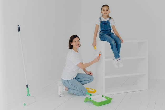 Shot of lovely mother and small hard working daughter pose in empty room Premium Photo