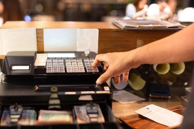 Shot in low light hand pressing electronic cash register in a shop. Premium Photo