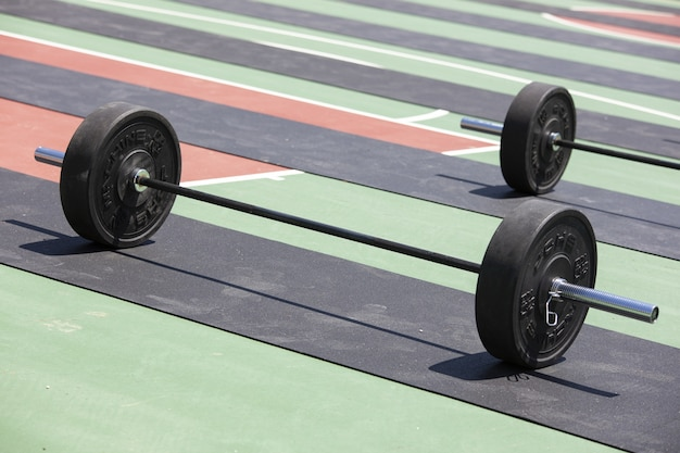 Shot of multiple barbells loaded with weight plates ready for weightlifting Free Photo