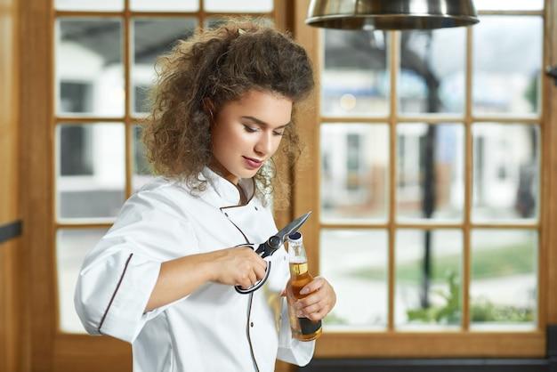 Снимок красивой женщины-шеф-повара, открывающей бутылку пива на кухне, профессии copyspace, пить алкоголь, пить напитки, релаксация, расслабиться концепция. Бесплатные Фотографии