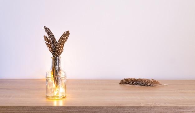 Снимок пары перьев, сложенных вместе и помещенных в стеклянную вазу. Бесплатные Фотографии