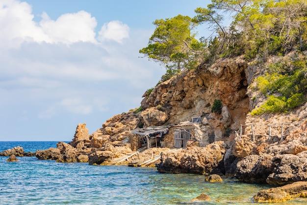 大きな石の塊に囲まれた崖の下に建てられた海辺の小屋のショット 無料写真