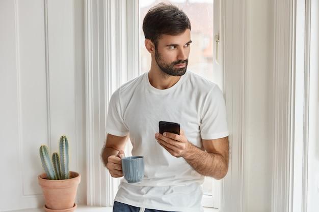 흰색 티셔츠에 수염을 기른 백인 남자의 총, 휴대 전화와 커피 머그잔을 들고, 새로운 응용 프로그램을 설치하고, 무료 인터넷을 즐기고, 옆으로 집중하고, 저녁 식사를 위해 식당에서 음식을 주문하고, 커피를 마신다. 무료 사진