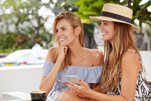 Снимок: красивые женщины отдыхают в уютном ресторане, используют современные технологии для совершения покупок в интернете, радостно смотрят на портативный компьютер, используют кредитную карту для оплаты покупок, рады выпить кофе Бесплатные Фотографии