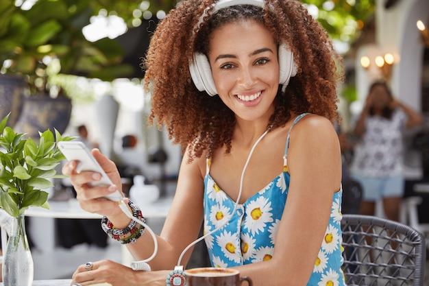 アフロの髪型を持つ美しい黒肌の混血女性のショットは、現代のスマートフォンに接続されたヘッドフォンでお気に入りのトラックを聴きます 無料写真