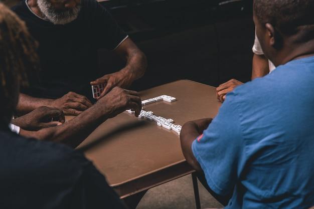 Выстрел из четырех африканских мужчин, играющих в домино на столе Бесплатные Фотографии