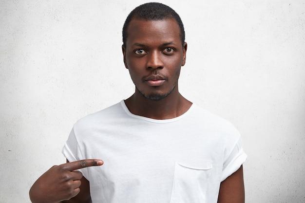 自信に満ちた表情のハンサムな深刻な若いアフリカ男性のショットは、ロゴや広告コンテンツのtシャツに人差し指で示しています。 無料写真