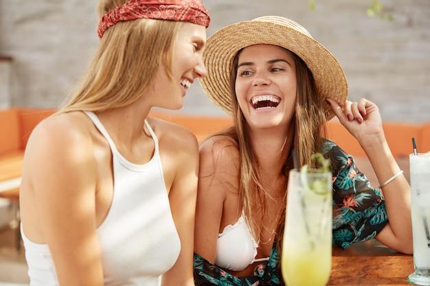 Снимок счастливой женщины в модной летней шляпе и блузки сидит в кафе со свежим коктейлем Бесплатные Фотографии