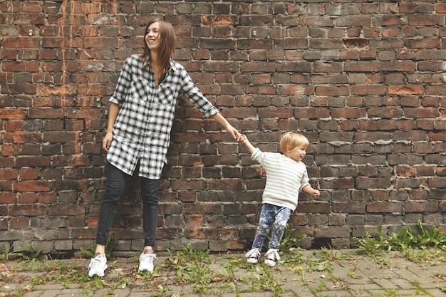レンガの壁の近くの散歩に金髪少年と少女のショット。小さなおばさんが大人の叔母さんを引っ張って去っていきます。チェックシャツの白人の女の子は頑固です。反対側を見ている2人。 無料写真