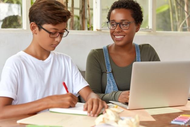 作業プロセスに関与する多民族のティーンエイジャーの学生のショット、ポータブルラップトップコンピューターで情報を閲覧する、メモ帳でプロジェクト作業のアイデアを書く、デスクトップに座る、収入メッセージを確認する 無料写真