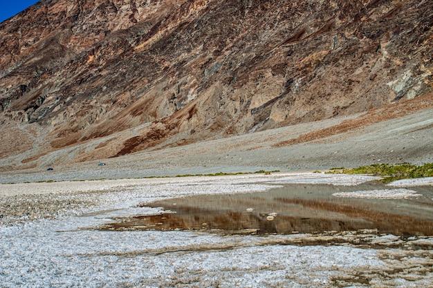 岩だらけの丘の前の部分的に乾燥した水たまりのショット 無料写真