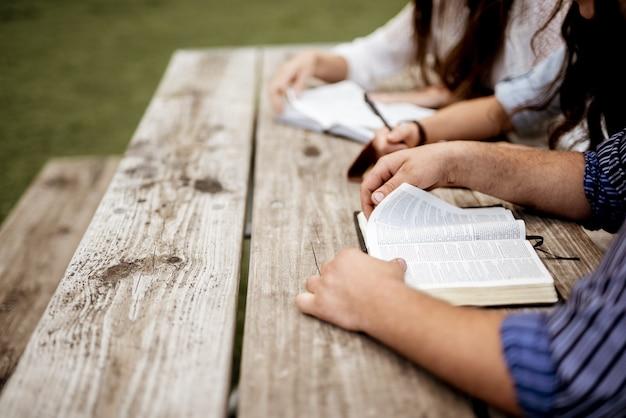 서로 가까이 앉아 성경을 읽는 사람들의 총 무료 사진