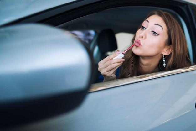彼女の車に座ってバックミラーを見て、口紅をつけて化粧をしているきれいな女性ドライバーのショット 無料写真