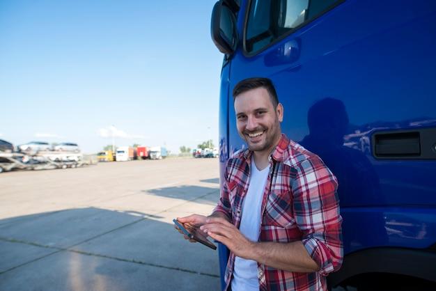 Снимок профессионального водителя грузовика, стоящего у своего грузовика с планшетом и настраивающего gps-навигацию для следующей поездки Бесплатные Фотографии