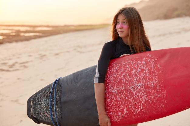 Снимок серфингистки в черном купальнике, держащей доску для серфинга, прогулки по морю или океану Бесплатные Фотографии
